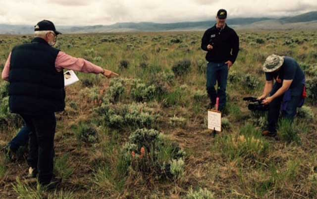 A group of ranchers work together to set up a landscape photograph at a BLM photo point during a range monitoring workshop in Oreana while Life on the Range videographer Chris Ennis documents the story.