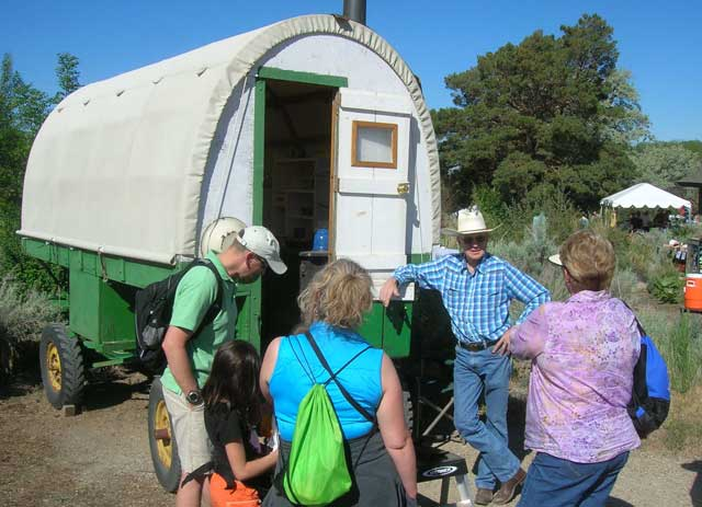 James England talks to folks about sheep camp wagons. England's father refurbished this one on display