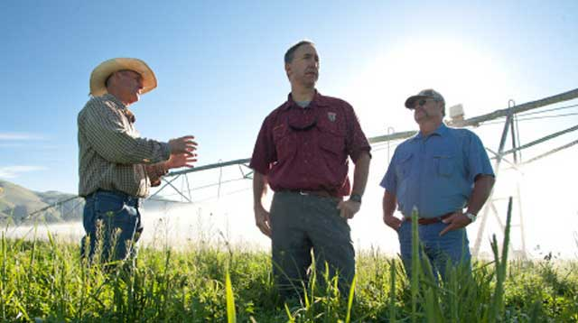 Leadore Rancher Merrill Beyeler talks with agency officials after installing a pivot sprinkler on his ranch. Beyeler has converted to sprinkler irrigation to leave more water in the river and tributary streams for fish. (Photo by Mark Gamba)
