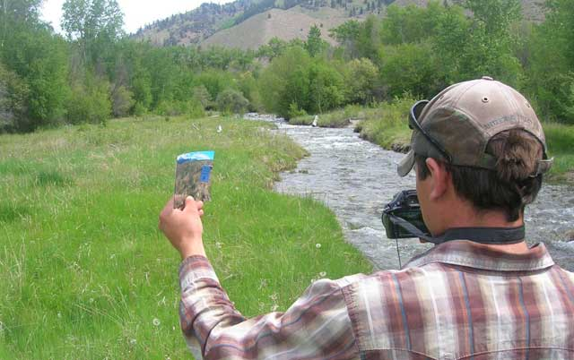 Seth McFarland uses a previous monitoring photo to help him find the same photo point he used previously. Here, he's documenting ecological conditions in a mead-ow along Carmen Creek on the McFarland Ranch. The family's objectives for the meadow are to improve wildlife habitat and create forage for fall livestock grazing.