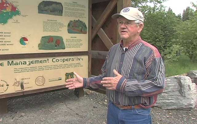 Butch Klaveano explains the formation of the Emerald Creek Management Cooperative by the educational multiple use sign in Fernwood