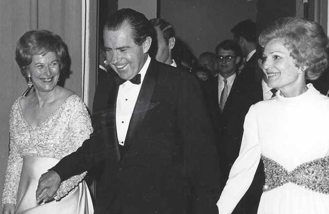 John's political career began in 1969 when he was appoint- ed to the Idaho State Senate to replace his mother, Mary Brooks, left, who was tapped by President Nixon to run the U.S. Mint. Nixon's wife, Pat, is on the right.